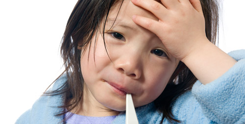 Little girl, clutching her forehead with a thermometer in her mouth